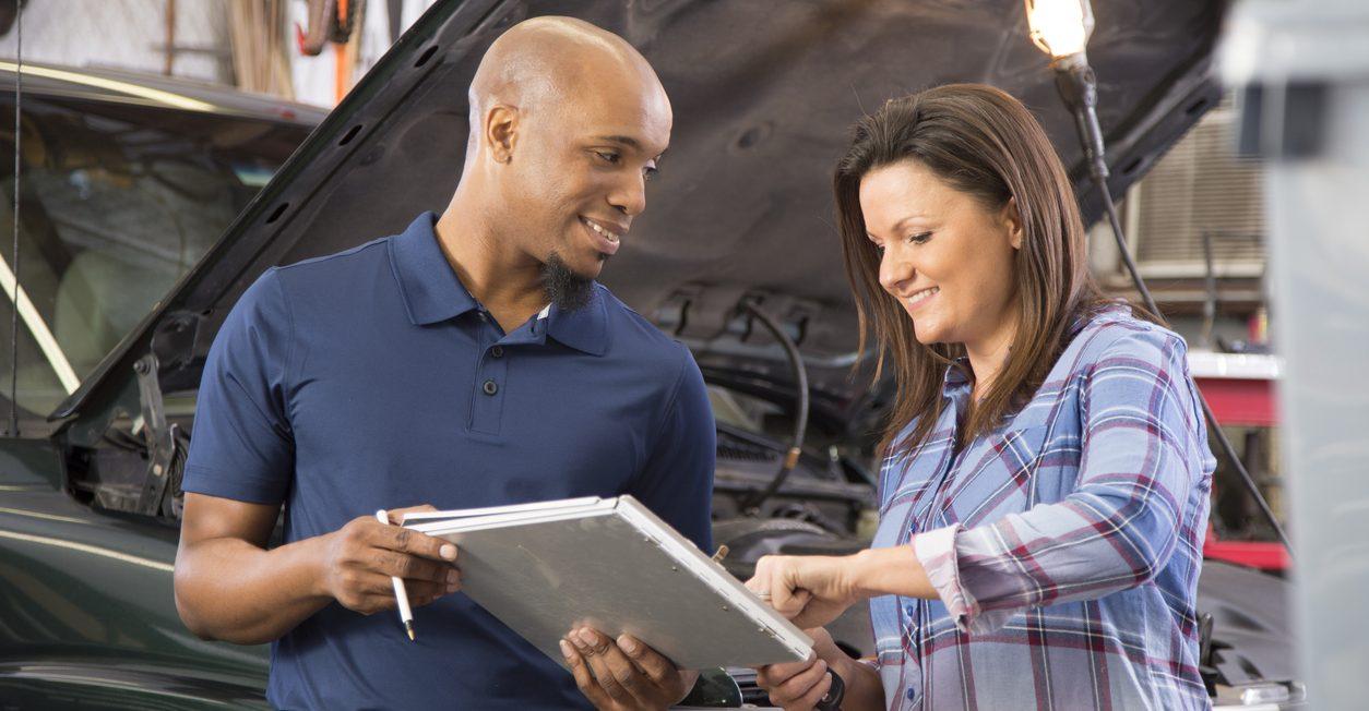 Mechanic explains vehicle repair invoice to customer in auto repair shop